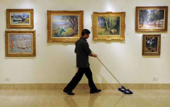 A gallery maintenance staff sweeps the floor past paintings