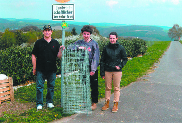 Helping to unroll new sheep fencing above the Rhine River near Holzfeld, Germany are American-and-German cousins (from left) David Hay, Somerset County; and his eighth cousins Jonathan and Hannah Höh, whose father, Hartmut Höh enjoys raising sheep as a hobby.