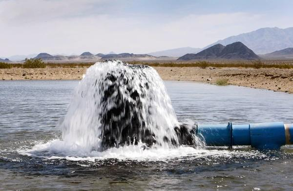 Water pours out into a spreading basin that holds water from a pilot well used for testing. Cadiz Inc. hopes to pump groundwater from the Mojave Desert to sell to urban Southern California.
