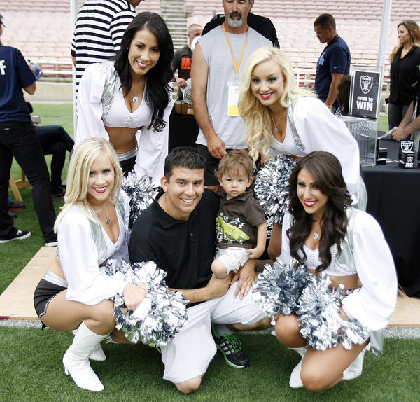 Joe Perez, of Temple City, holds his son Averey, 1, as they get their picture taken with the Raiderettes of the Oakland Raiders at the Rose Bowl in Pasadena for the NFL All-Access Event.