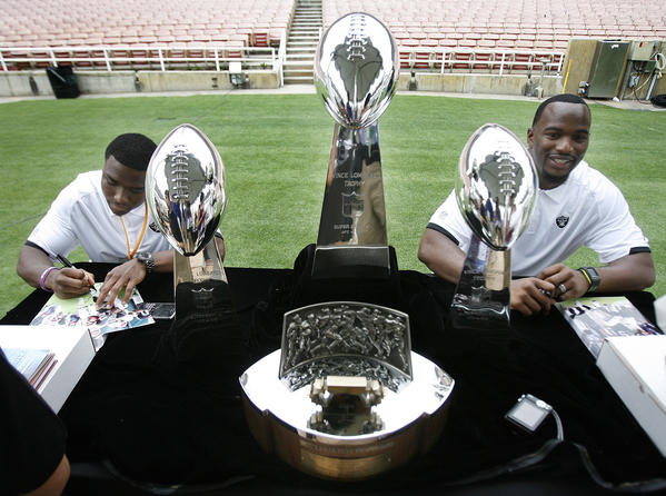 Jacoby Ford and Marcel Reece, of the Oakland Raiders, with three Vince Lombardi Trophies and a Lamar Hunt Trophy on their table, sign autographed pictures of themselves at the Rose Bowl in Pasadena for the NFL All-Access Event.