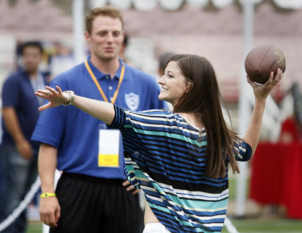 With her NFL quarterback boyfriend Greg McElroy watching, Meredith Gray, of Decatur, AL, winds up to throw the football into a target at the Rose Bowl in Pasadena for the NFL All-Access Event.