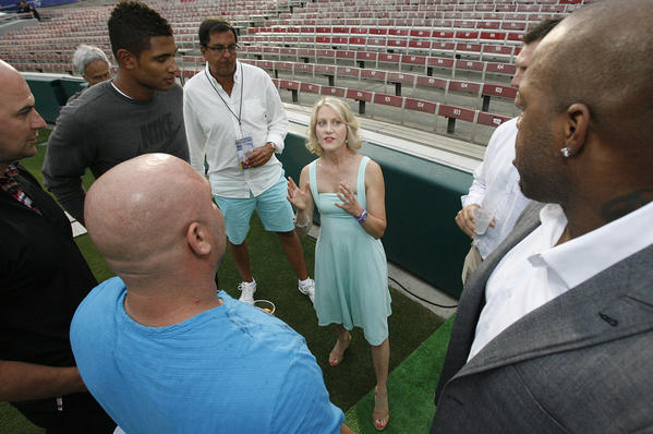 Andrea Kremer, of NBC and HBO Sports, is dwarfed in a huddle with NFL football players at the Rose Bowl in Pasadena for the NFL All-Access Event.