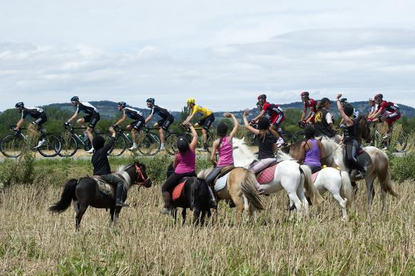 Young fans on horses wave to the pack with Overall leader's yellow jersey, British Bradley Wiggins, riding in the 226 km and twelfth stage of the 2012 Tour de France cycling race starting in Saint-Jean-de-Maurienne and finishing in Annonay Davezieux, southeastern France.