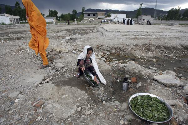 A Pakistani girl washes vegetable at the site of the demolished compound of slain Al-Qaeda leader Osama bin Laden in northern Abbottabad on May 1, 2012,  ahead of bin Laden's first death anniversary.