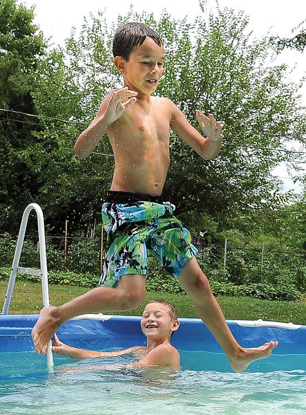 Five-year-old Conner Thorn hits the surface of the water after doing a flip off a ladder Thursday afternoon.