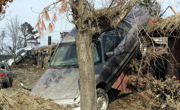 In the top 5 - 2005 coverage of Hurricane Katrina.  Two cars rest against a house in Meraux, La., Wednesday, Nov. 9, 2005.  A massive tank in the adjacent Murphy Oil Corp. refinery floated off its base and broke during Hurricane Katrina, spilling crude oil into about 1,700 homes.