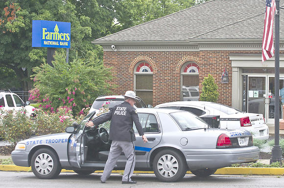 A Kentucky State Trooper arrives at Farmers National Bank in Perryville Friday afternoon after a man tried to force a bank employee to remove money from an ATM.