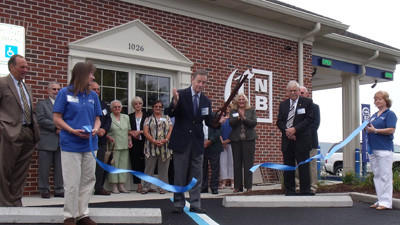 Tellers Laura Maust and Connie Slope hold the ceremonial ribbon as Bob Philson, Citizens National Bank chairman of the board, cuts the ribbon marking the bank's grand opening.