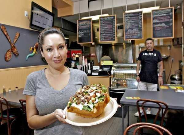 With owner Jordi De Riquer in the background, Liz Villalva of Iguana Ranas: Tacos on Brand shows the steak taco salad, which includes beans, lettuce, queso fresco, pico de gallo, guacamole and ranch dressing in a tostada shell, at the Glendale restaurant.