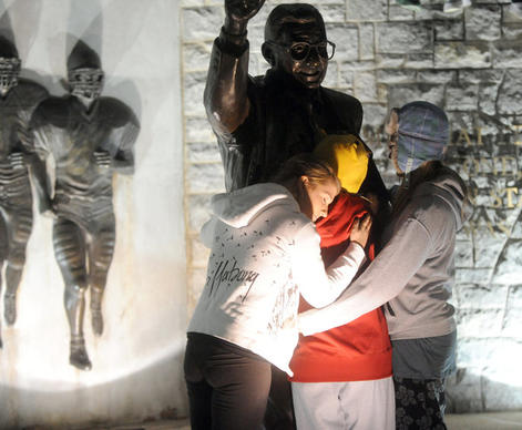 The Penn State University students, many in tears, gather around the statue of Coach