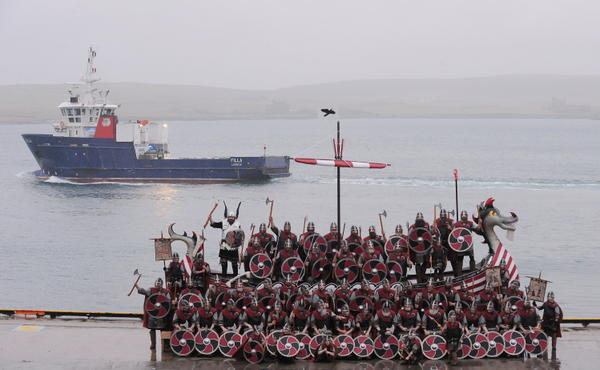 Members of the Viking Jarl Squad pose for pictures with a Viking Galley ship as a ferry passes them on the morning of the annual Up Helly Aa Festival, in Lerwick, Shetland Islands, on January 26, 2010. Up Helly Aa celebrates the influence of the Scandinavian vikings in the Shetland Islands and has employed this theme in the festival since 1870. The event culminates with up to 1000 'guizers' (men in costume) throwing flaming torches into a Viking longship later.