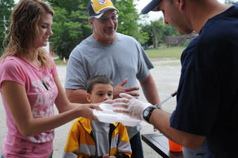 Amber Swanson, 17, father Chris Swanson and brother Dillon, traveled from Toccoa, Ga., to celebrate the anniversary of her rescue with a barbecue at the Sipesville fire department. Five years ago Swanson went missing in the woods near Beam Rocks. Firefighter Scott Kovach is seen serving food.