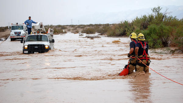 Imperial County firefighters Mark Jackson and Diego Galindo make their way to an Imperial Irrigation District employee who was stranded on Dunaway Road north of Interstate 8 on Friday.