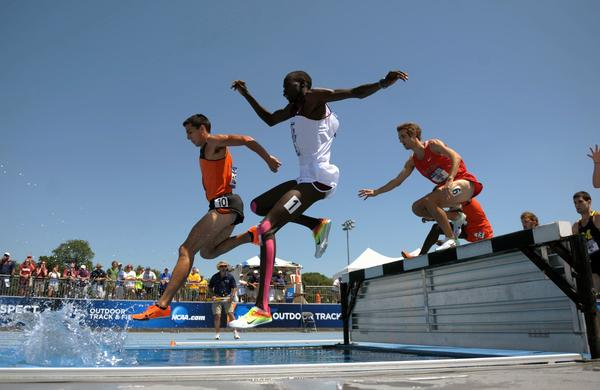 Glastonbury's Donn Cabral leads the pack over the hurdle and into the water pit during the 2012 NCAA steeplechase championship in Iowa.