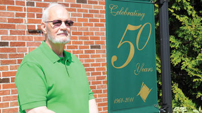 Dr. James M. Snider stands near a sign that makes him proud. He has worked for the Allegany Community College of Maryland for 33 years. He was one of the driving forces behind the development of the ACM Somerset campus, and he is the current vice president of Pennsylvania campuses for ACM, that also include a Bedford campus.