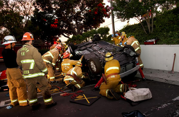 Burbank firefighters remove a woman who was trapped in her car after it turned over.