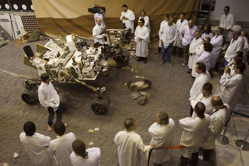 Scientists at the Jet Propulsion Laboratory in La Cañada Flintridge gather around a replica of the Mars rover Curiosity. After a journey of nearly nine months, the six-wheel laboratory is scheduled to touch down on the Red Planet at 10:31 p.m. PDT on Aug. 5.