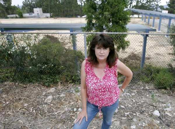Melody McCormick stands in her neighbor's yard at 2320 El Moreno St. where a good look at the solar panel structure being erected can be seen on the campus of Mountain Avenue Elementary School in La Crescenta.