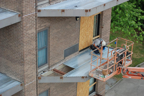 A worker lays down a new balcony outside a unit at Arnold Tower.