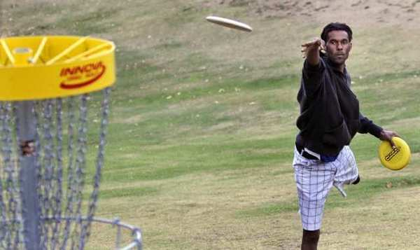 "Philo Brathwaite uses a ""putting disc"" on the 11th green disc catcher at the Verdugo Hills Golf Course in Tujunga."