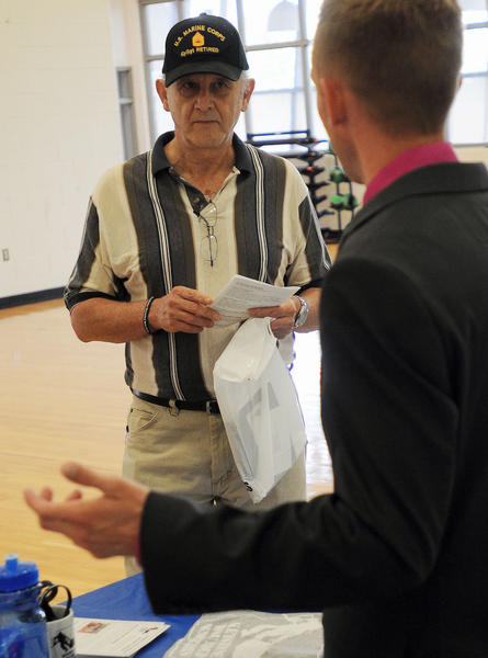 Russell Easley of Allentown, a U.S. Marine Corps. veteran, listens as Jonathan Tompkins, of the Keystone Wounded Warriors, explains how his organization helps veterans find jobs and with financial hardships, during a job fair hosted by Congressman Charlie Dent on Saturday at the Lehigh Carbon Community College gymnasium in Schnecksville.