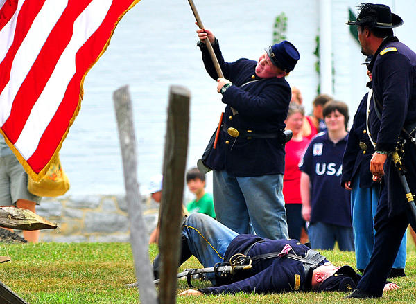 Union flag-bearer strains to swing large Union flag Saturday during reenactment of Civil War engagement in Williamsport.
