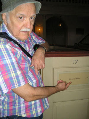 Dan Norvell points toward the Jefferson pew in Bruton Church in Williamsburg, Va.