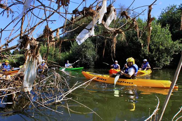 Trash bags hang from bushes along the Los Angeles River as kayakers from L.A. Conservation Corps pass through on an inspection tour of the river Saturday.
