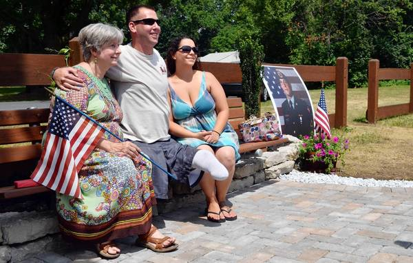 Jesse Reed's mother, Dolores (left), sits with Reed's best friend, Adam Keys, and Reed's wife, Heather on a bench dedicated to Reed's memory along the Ironton Rails to Trails.