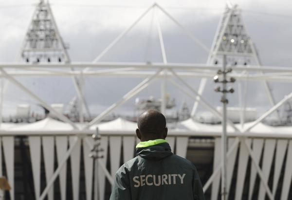 A security guard walks towards the Olympic Stadium in the London 2012 Olympic Park at Stratford in London July 13, 2012.  Britain's air force will be on standby to shoot down any rogue aircraft over London from Saturday under tight new restrictions being enforced two weeks ahead of the Olympic Games. Security surrounding the Olympics has made the headlines this week after Britain was forced to deploy 3,500 extra troops to fill an embarrassing last-minute shortfall in private security staff.
