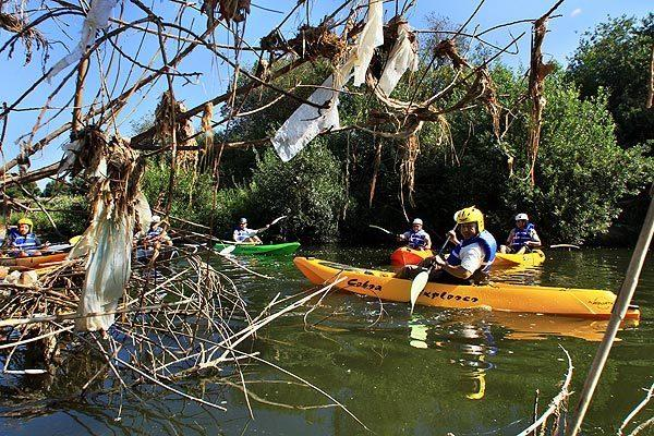 Trash bags hang from bushes along the Los Angeles River as kayakers from the L.A. Conservation Corps do an inspection tour.