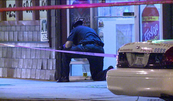 A police evidence technician at the scene of a shooting in the 1200 block of West 79th Street that left a 27-year-old man dead.