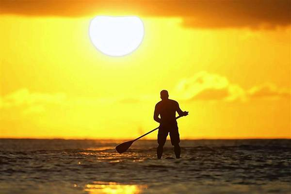 File photo of paddle board rider surfing at sunset on New Year's Eve at Waikiki Beach in Honolulu