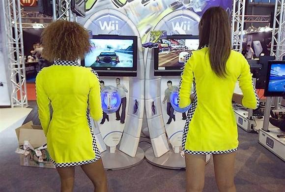 Hostesses play Wii games during the video game show in Paris