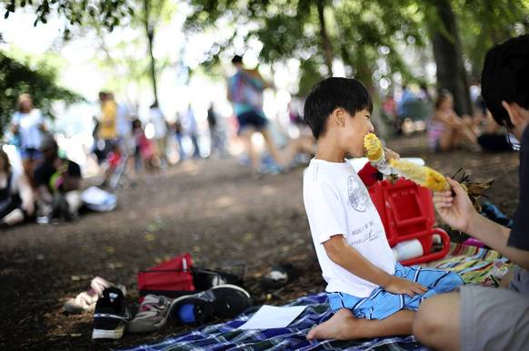 Xander Hwang, 8, of Glenview,  eats corn on the cob in the shade with his family on the last day of the Taste of Chicago in Chicago