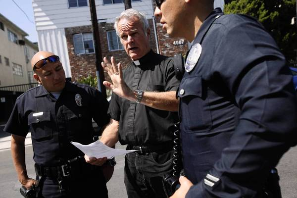 Rev. Christopher Kelley talks to police at St. Mary of the Angels Anglican Church in Loz Feliz, where things have become so polarized that he and his supporters were locked out by their opponents.