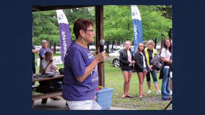 The crowd at the Windber Relay For Life listens intently to Gaynelle Schmieder as she tells her story about her fight against cancer. Schmieder was the guest speaker at the Windber Relay For Life held this weekend at Windber Recreation Park.
