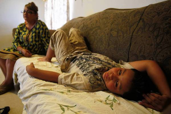 Marco Cisneros relaxes on the sofa watched by his mother, Susana. Marco, who has asthma, has visited the hospital 50 times and been airlifted several times.