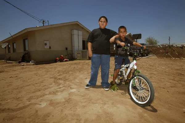 Brothers Esteban and Angel Valenzuela play in the dirt-covered backyard of their El Centro home.