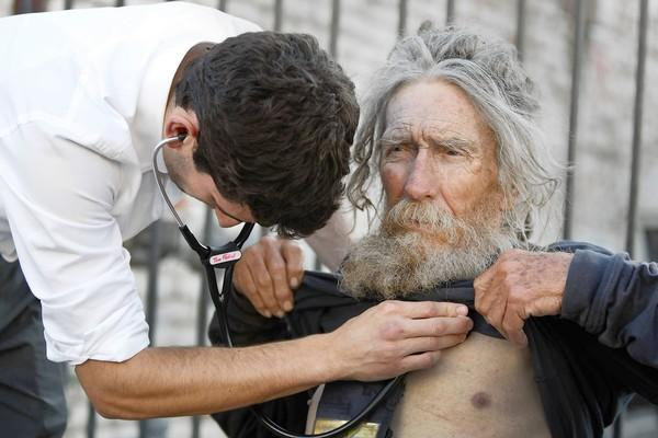 "Tom Fadial, a third-year UCLA medical student, listens to the heart of patient Stanley Rudolph, 75, a homeless Korean War-era veteran, who took advantage of services offered by the Mobile Clinic Project. ""I'm what they call off the grid,"" Rudolph said."