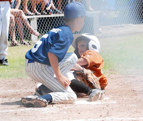 Jamie Janicki of Harbor Springs (right) slides safely under the tag applied by Gabe Whitmore of Petoskey Sunday during a Little League Minors Division (ages 9-10) district title game in Harbor Springs. Harbor won, 10-1, to claim the district title.