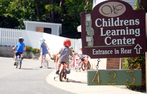 Children ride their bikes outside of the Women's Resource Center's Children's Learning Center.