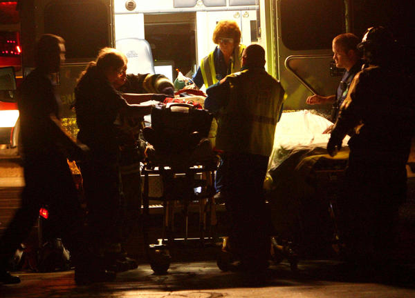 Rescue workers stabilize a patient for airlift after he was injured in a rollover accident after a police chase in Antioch that killed one person and injured two others.