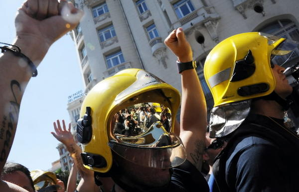 Firefighters and other government employees take part in a demonstration against the Spanish government's latest austerity measures, in front of the Spanish Parliament (Las Cortes) in Madrid, on July 16, 2012. Several hundreds government workers, including police officers, firefighters, and healthcare workers, joined the spontaneous protest after conservative Prime Minister Mariano Rajoy announced, on July 13, the latest measures to lower Spain's deficit, a 65-billion-euro (80 billion USD) austerity package involving among other things an increase in the VAT (TVA) tax and cuts in unemployment benefits.