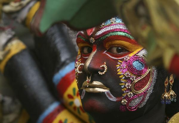 "A performer looks on as he takes part in the annual Hindu religious festival of Bonalu in the southern Indian city of Hyderabad July 16, 2012. The word ""Bonalu"" is derived from the Telugu language word ""Bhojanalu"", the food offered to Goddess Kali, the Hindu goddess of power."