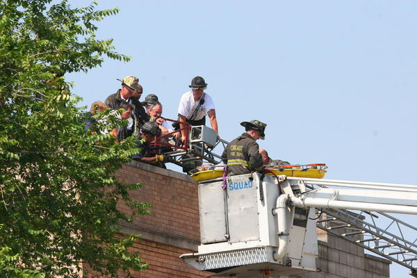 Chicago Fire Department crews bring the victim of a building collapse in West Pullman down from an adjacent building that did not fall this morning.