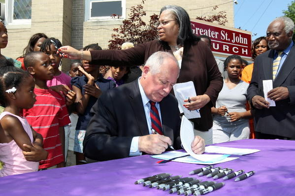 Gov. Pat Quinn, joined by Ald. Deborah Graham, 29th, and Congressman Danny Davis, signs three new laws to increase assistance for crime victims and their families outside Greater St. John Church.