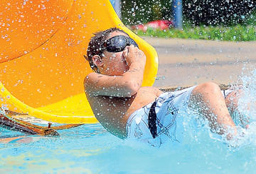 "John-Michael Frye, 10, of Clear Spring beats Monday's heat by sliding into the pool at Martin L. ""Marty"" Snook Memorial Park in Halfway."