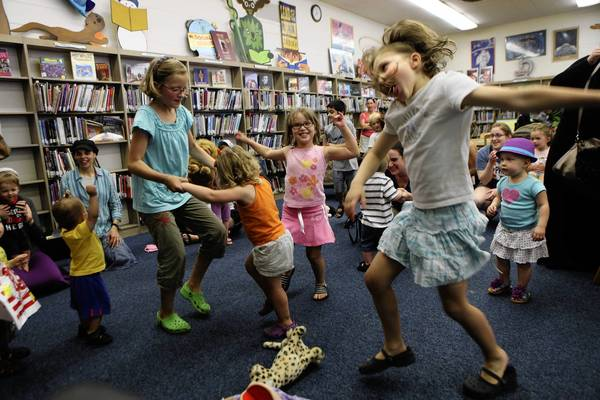 Children dance and sing Monday during story time at Chicago's Northtown Branch Library, where Mayor Rahm Emanuel and Library Commissioner Brian Bannon announced that the libraries will be open all day on Mondays in the fall.